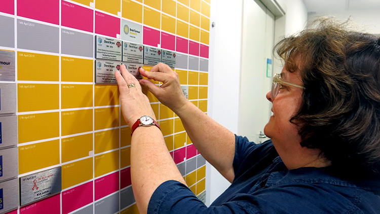 Clarion Housing Group CEO, Clare Miller, places a tile on the Wall of Hope at Queen Mary University of London Brain Tumour Research Centre of Excellence lab.